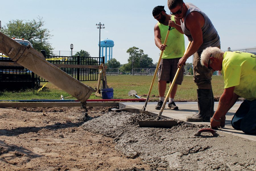 Workers pour cement for a sidewalk project.
