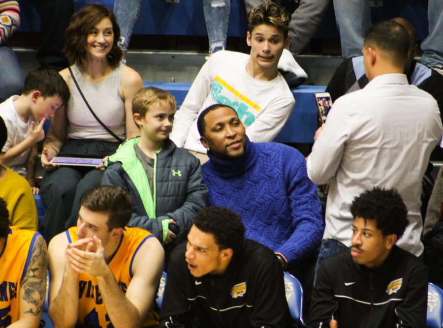 Shawn Marion (center) poses for a photo with a young fan during the men's basketball game in the PE Complex.