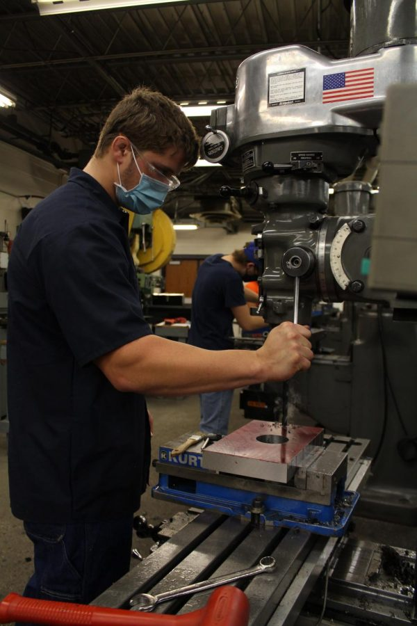 A student in the Precision Machining program uses a machine while wearing a mask.