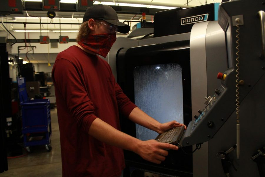 A student in the precision machining program uses equipment while taking precautions.